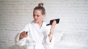 La mujer hermosa quita la máscara de limpiamiento de cara en el fondo blanco del ladrillo almacen de metraje de vídeo
