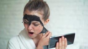 La mujer hermosa quita la máscara de limpiamiento de cara en el fondo blanco del ladrillo metrajes