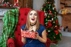 La mujer hermosa recibe un regalo y una alegría Año Nuevo del concepto, feliz Imagen de archivo libre de regalías