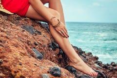 La mujer hermosa relaja sentarse en la roca por el mar Primer de piernas femeninas Fotos de archivo
