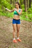 La mujer hermosa sana joven está haciendo una yoga en el parque verde Fotos de archivo