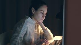 La mujer hermosa se cae trabajo dormido en el ordenador portátil en la noche almacen de metraje de vídeo