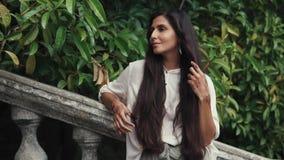 La mujer hermosa se endereza el pelo con sus manos, en las cuales hay un tatuaje de la alheña almacen de metraje de vídeo