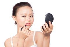 La mujer hermosa se está aplicando los labios con el lápiz labial rojo Imagen de archivo