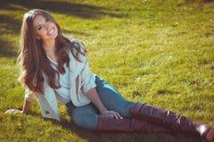 La mujer hermosa se está sentando en hierba en parque del otoño Imágenes de archivo libres de regalías