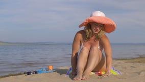 La mujer hermosa se está sentando en la playa y la arena de colada de sus manos