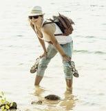 La mujer hermosa se está colocando en el lago y sostiene sus zapatos Imagenes de archivo