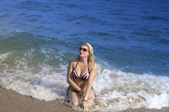 La mujer hermosa se sienta adentro salpica de una resaca de ondas azules Foto de archivo