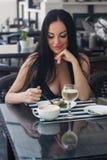 La mujer hermosa se sienta en un café y come la torta Imagen de archivo