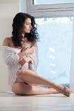 La mujer hermosa se sienta en una ventana fotos de archivo libres de regalías