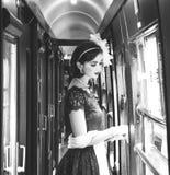 La mujer hermosa se vistió en vestido rojo del té del vintage del té en el tren locomotor fotos de archivo