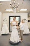 La mujer hermosa se vistió para arriba como novia con el empleado mayor que ayudaba en tienda nupcial Imagen de archivo