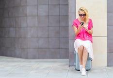 La mujer hermosa sienta en el reloj de la maleta el teléfono Fotos de archivo