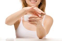 La mujer hermosa sienta un tarro de crema de la mano Foto de archivo