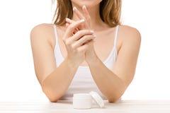 La mujer hermosa sienta un tarro de crema de la mano Imagen de archivo