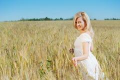 La mujer hermosa sonríe en un campo Imágenes de archivo libres de regalías