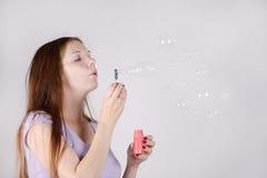 La mujer hermosa sopla burbujas de jabón Imagen de archivo