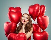 La mujer hermosa sostiene los globos rojos del corazón Sorpresa, tarjetas del día de San Valentín gente y concepto del día de tar imagen de archivo libre de regalías