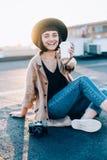 La mujer hermosa sostiene la taza de café en puesta del sol Fotos de archivo