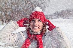 La mujer hermosa tiene una bola de nieve en un casquillo rojo fotografía de archivo