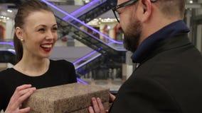 La mujer hermosa toma el presente de un hombre en chaqueta negra metrajes