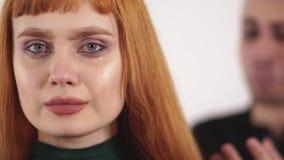 La mujer hermosa trastornada de los jóvenes con el pelo largo rojo está llorando y el hombre enojado joven está gritando detrás d almacen de video