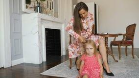 La mujer hermosa trenza la trenza de su pequeña hija almacen de video