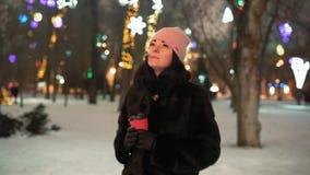 La mujer hermosa visita la iluminación de la Navidad en los árboles en el parque almacen de video