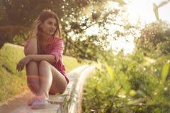 La mujer hermosa y atractiva que se sienta en un lado, dril de algodón casual atractivo que lleva pone en cortocircuito Fotografía de archivo