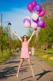 La mujer hincha, altura completa, parque de la ciudad, salto Fotos de archivo