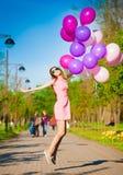 La mujer hincha, altura completa, parque de la ciudad, salto Foto de archivo