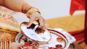 La mujer hindú sostiene la cubierta de acero sobre la placa con arroz y la vela metrajes