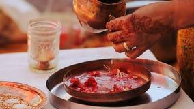 La mujer hindú toma la figura del cuenco del grom de dios con los pétalos almacen de metraje de vídeo