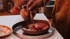 La mujer hindú vierte el aceite sobre los pétalos metrajes