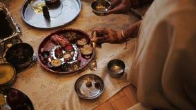 La mujer hindú vierte el agua de la cuchara sobre las nueces en la placa de plata almacen de video