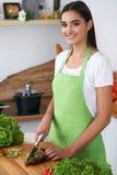 La mujer hispánica joven está cocinando en la cocina El ama de casa está cortando verduras y la carne verde para la ensalada fres Foto de archivo