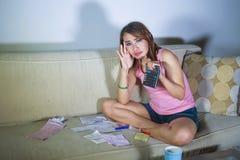 La mujer hispánica subrayada y preocupante atractiva joven con la calculadora y los recibos que calculaban costos mensuales y la  fotos de archivo