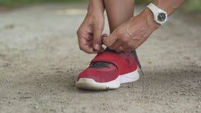 La mujer implica cordones en las zapatillas de deporte antes de activar metrajes