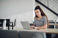 La mujer independiente atractiva está trabajando en proyecto, usando Wi-Fi en su ordenador portátil, sentándose en la tabla de ma Fotos de archivo