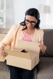 La mujer india joven feliz con el paquete encajona en casa Imágenes de archivo libres de regalías