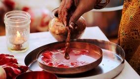 La mujer india pone el aceite en la placa con los pétalos y agua almacen de metraje de vídeo