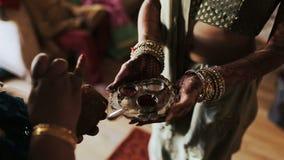 La mujer india sostiene la placa con gomas mientras que otro pinta el cocounut almacen de metraje de vídeo
