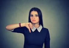 La mujer infeliz que da el pulgar abajo gesticula la mirada con la desaprobación Imagenes de archivo