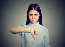 La mujer infeliz que da los pulgares abajo gesticula la mirada con la expresión negativa Fotografía de archivo libre de regalías