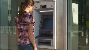La mujer inserta la tarjeta de actividades bancarias en la atmósfera almacen de video