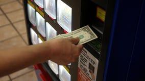 La mujer inserta un billete de dólar en una máquina de la lotería metrajes