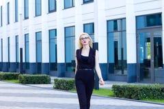 La mujer inteligente camina abajo de la calle contra la perspectiva del centro de negocios Fotos de archivo