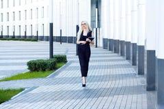 La mujer inteligente con el cuaderno camina abajo de la calle contra la perspectiva del centro de negocios Imagenes de archivo