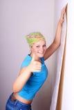 La mujer intenta encendido los papeles pintados para emparedar Foto de archivo libre de regalías