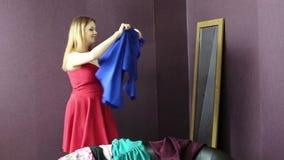 La mujer intenta encendido un vestido cerca del espejo almacen de metraje de vídeo